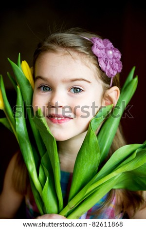 Portrait of a sunny child girl with tulips on a dark background - stock photo