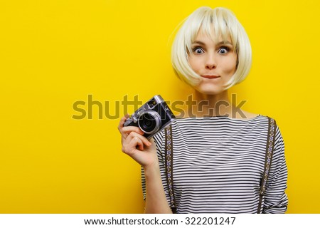 Portrait of a surprise girl with a camera in hand on a yellow background. Isolated studio. Blonde girl. - stock photo