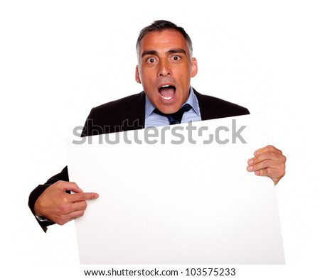 Portrait of a surprised businessman pointing and holding a white card with copyspace on isolated background - stock photo