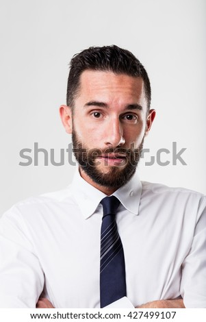 portrait of a surprised businessman with his arms folded - stock photo