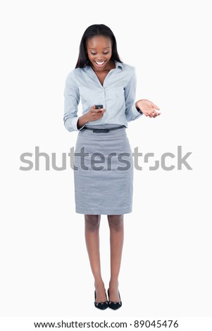 Portrait of a surprised businesswoman reading a text message against a white background - stock photo