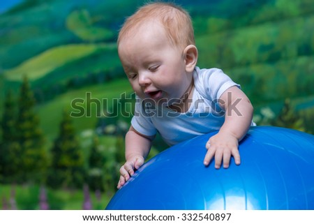 Portrait of a surprised child. Close-up portrait of the baby, on blue ball. - stock photo