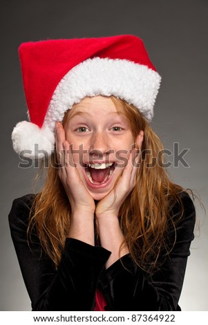 Portrait of a surprised girl wearing a Santa hat. - stock photo