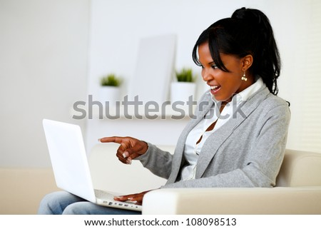 Portrait of a surprised woman pointing to laptop screen while is sitting on sofa at home - stock photo