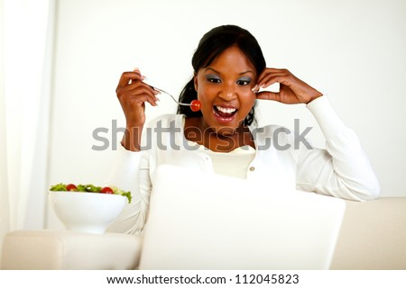 Portrait of a surprised young woman eating fresh vegetable salad while is sitting in front of her laptop. with copyspace - stock photo