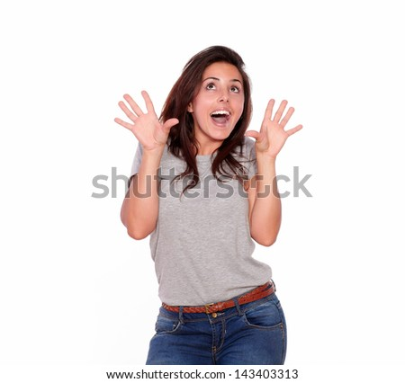 Portrait of a surprised young woman in jeans screaming with hands up on isolated background - copyspace - stock photo