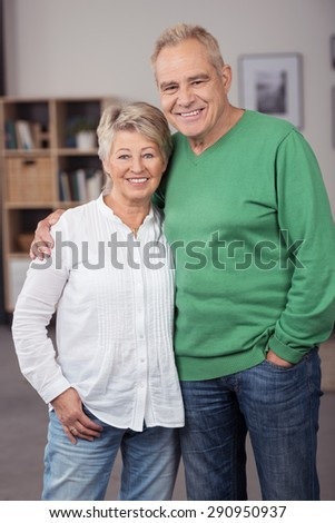 Portrait of a Sweet and Happy Middle Aged Couple in Casual Clothing Posing Inside their Home and Smiling at the Camera - stock photo