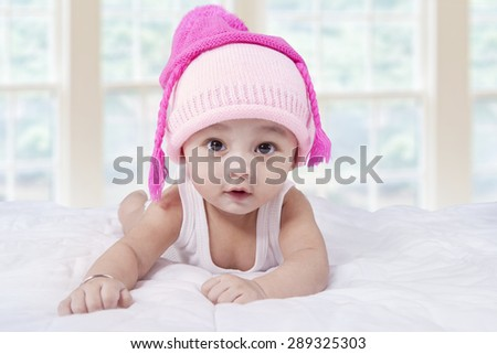 Portrait of a sweet baby boy lying on bed while wearing hat and look at the camera - stock photo