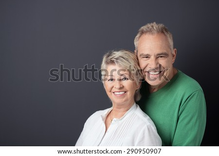 Portrait of a Sweet Matured Couple Smiling at the Camera Against Gray Background with Copy Space on the Left Side. - stock photo