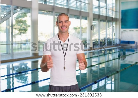 Portrait of a swimming coach gesturing thumbs up by the pool at leisure center - stock photo