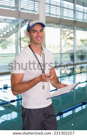 Portrait of a swimming coach with stopwatch by the pool at the leisure center - stock photo