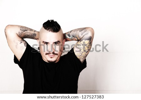 Portrait of a tattooed relaxed, hispanic man. - stock photo