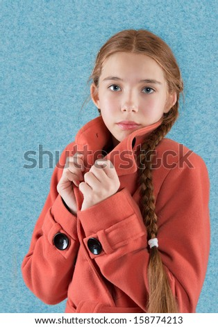 Portrait of a teen girl in red overcoat on blue background - stock photo