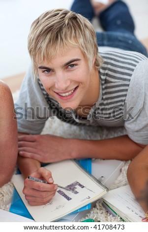 Portrait of a teen guy doing homework on the floor - stock photo