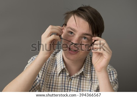 Portrait of a teenage boy looking over his glasses - stock photo