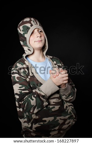 Portrait of a teenage boy on a black background - stock photo