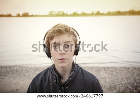 portrait of a teenage boy with headphones at a riverbank, toned image - stock photo