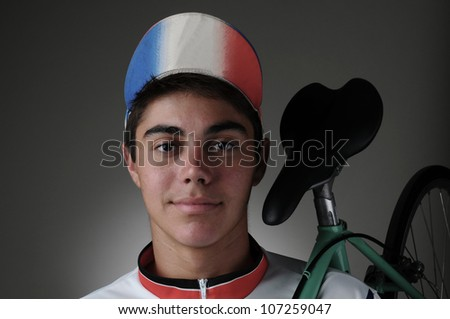 Portrait of a teenage cyclist holding a bicycle on his shoulder. Closeup in horizontal format with a gray light to dark background. - stock photo