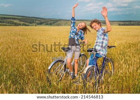 Portrait of a teenage girl and a boy raised his hands in salute against the blue cloudy sky and yellow field of rye - stock photo