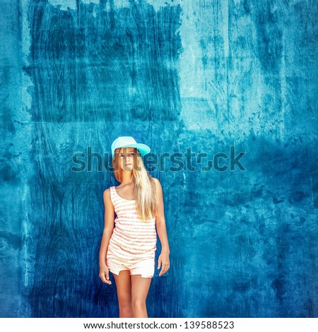 Portrait of a teenage girl in the cap with a blue wall - stock photo