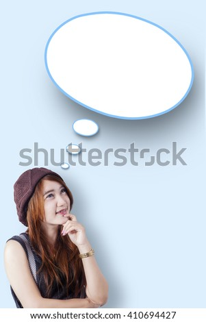 Portrait of a teenage girl looking at a blank speech bubble in the studio - stock photo