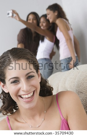 Portrait of a teenage girl smiling with her friends in background. - stock photo