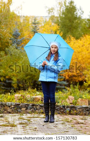 Portrait of a teenage girl walking around in the park on a background of yellow autumn leaves - stock photo