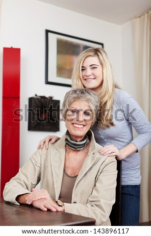 Portrait of a teenage girl with her grandmother at home - stock photo