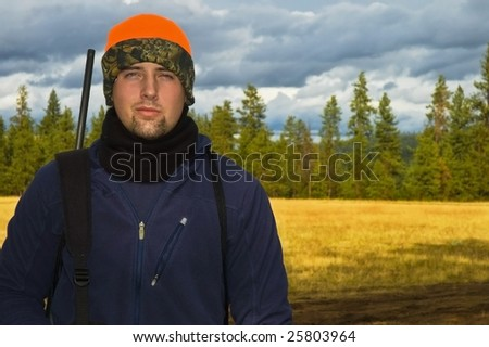 Portrait of a teenage hunter posed in front of a open meadow background. - stock photo