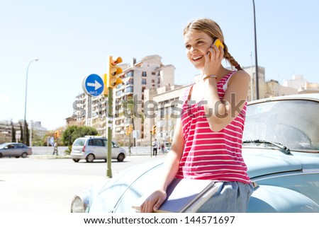 Portrait of a teenager girl having a conversation with her smartphone while sitting on a classic colorful car in a city during a sunny day with a blue sky, smiling. - stock photo