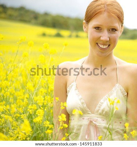 Portrait of a teenager girl relaxing on a large yellow flowers field during a summer vacation in the countryside on a sunny day. - stock photo