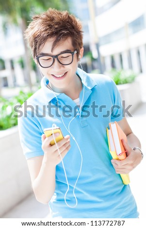 Portrait of a teenager listening to music on his mobile phone - stock photo