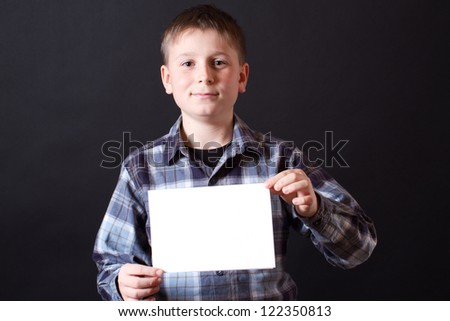 portrait of a teenager with a blank on a black background - stock photo