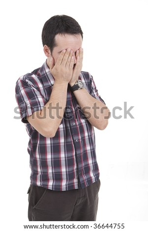 Portrait of a tensed young man with hands on the face - stock photo