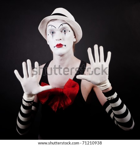 Portrait of a theater actor in makeup funny mime with a red bow on the chest in white hat and striped gloves on a black background - stock photo