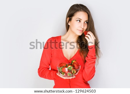 Portrait of a thoughtful brunette beauty eating strawberries. - stock photo