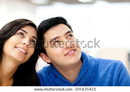 Portrait of a thoughtful couple  looking up and smiling - stock photo