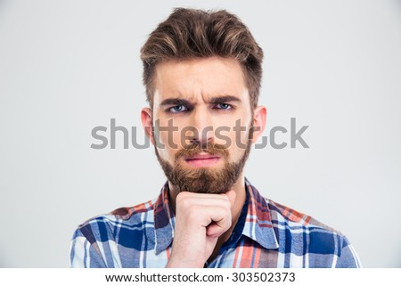 Portrait of a thoughtful man looking at camera isolated on a white background - stock photo