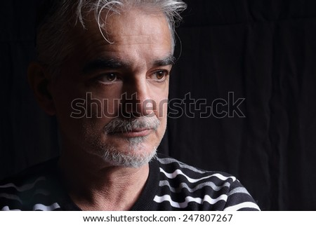 Portrait of a thoughtful senior man on black background.Closeup portrait of a man looking away - stock photo