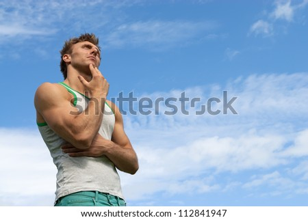 Portrait of a thoughtful strong man, on blue sky background. - stock photo