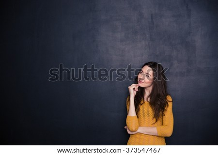 Portrait of a thoughtful woman looking away at copyspace over black background - stock photo