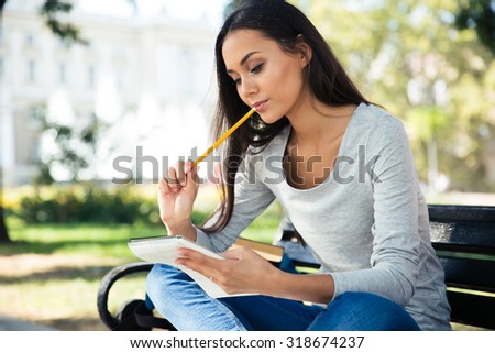 Portrait of a thoughtful woman sitting on the bench with pen and notepad outdoors - stock photo