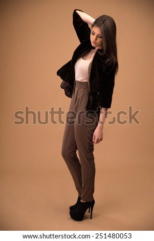 Portrait of a thoughtful young fashion woman over brown background - stock photo