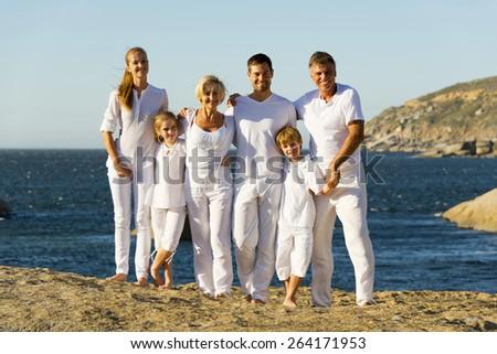 Portrait of a three generation family on a rocky coast. - stock photo
