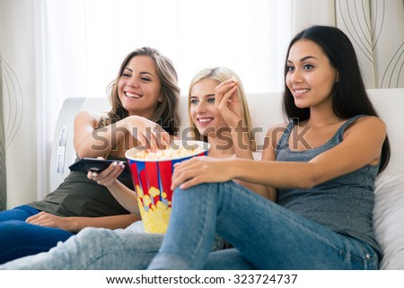 Portrait of a three happy girlfriends eating popcorn and watching tv at home - stock photo