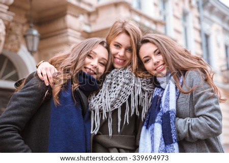 Portrait of a three smiling girlfriends standing together outdoors with old building on background - stock photo