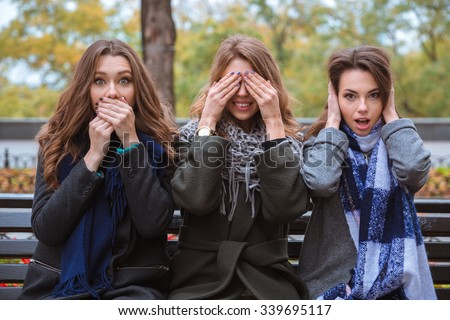 Portrait of a three women sitting on the bench and representing senses: mute, blind and deaf outdoors - stock photo