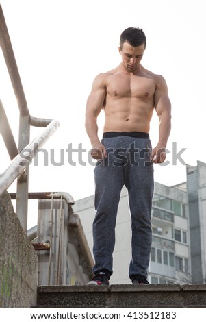 Portrait of a tired but satisfied with his training men runner resting after workout while sitting on the stairs outdoors, smiling young male jogger relaxing after intense exercising in the fresh air  - stock photo