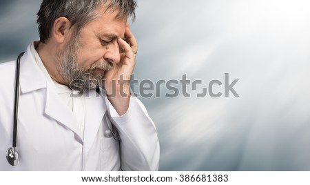 Portrait of a tired doctor with hand near his head, looking totally stressed out against blurred background with sun light and copyspace - stock photo