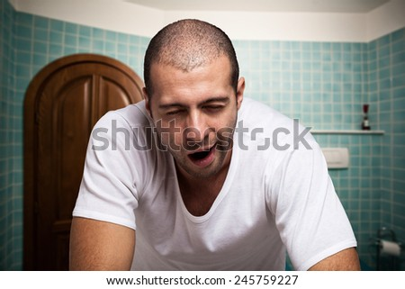 Portrait of a tired man looking in the mirror in his bathroom - stock photo